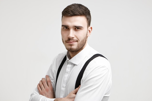 People, work, job, career and employment concept. picture of attractive self confident prosperous young male manager posing in studio with arms crossed and staring at camera with confident smile