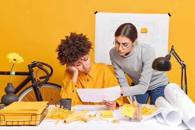La gente lavora il concetto di occupazione. le donne professioniste tristi e diverse cercano di decidere il problema con l'errore negli schizzi hanno alcune difficoltà che pongono nello spazio di coworking discutono del piano aziendale incentrato sui documenti