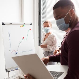 Le persone al lavoro in ufficio durante la pandemia indossano maschere mediche ed sono produttive