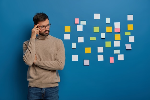 Persone, lavoro, concetto di pensieri. il ragazzo con la barba contemplativo tiene il dito sulla tempia, guarda pensieroso da parte, mette note adesive colorate sul muro