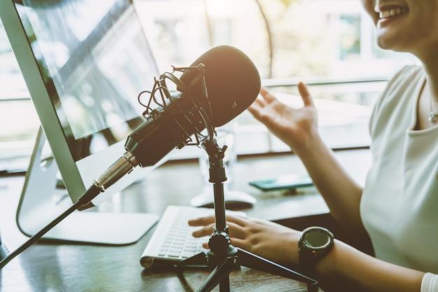 インターネットラジオ放送チャンネルのライブストリーミングトークミーティングやディスカッションクローズアップコンデンサーマイクを作るために家で働いている人々。