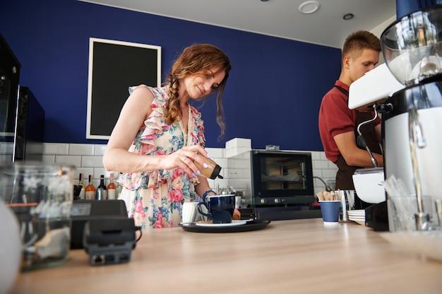 食堂のバーカウンターの後ろで働く人々。バリスタがコーヒーを準備し、シナモンパウダーをカプチーノの入ったカップに入れ、男性バリスタがスチームコーヒーマシンの後ろで働きます