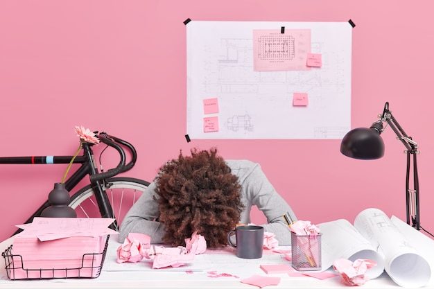People working exhaustion deadline concept. tired curly haired overworked woman leans at office desk works on future project surrounded with paper scraps sketches blueprints has lack of sleep