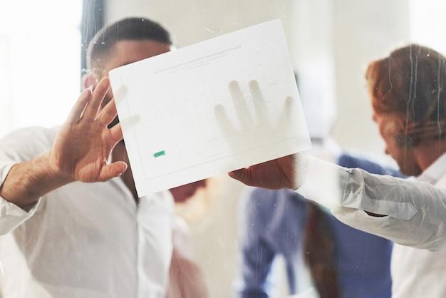사무실에서 일하고 종이에있는 정보를 사용하여 비즈니스 세부 사항에 대해 논의하는 사람들