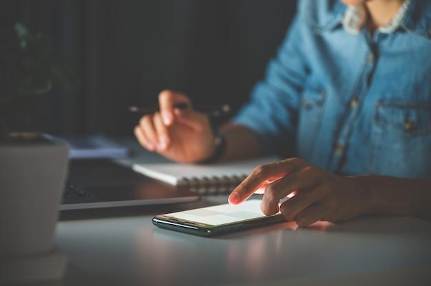 ラップトップ、携帯電話、ノートブック、またはコンピューターを使用して夜にオフィスで働く人々。ビジネスまたは在宅勤務の概念。