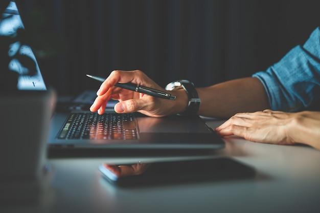 ラップトップ、ノートブック、またはコンピューターを使用して夜にオフィスで働く人々。