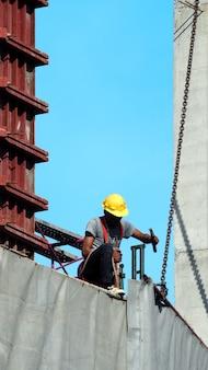 黄色いヘルメットと安全なロープ設備で建設現場で働いていて、灰色のビニールと青い空で建物を覆っている人々。