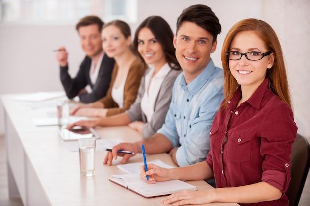 Люди работают вместе. группа молодых людей, сидящих за столом и улыбающихся в камеру