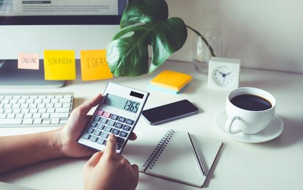 Люди, работающие с калькулятором на рабочем столе в офисе