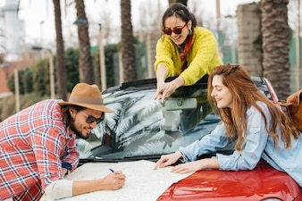 People writing on road map with pencil on car