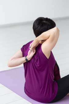 People, yoga, sport and healthcare concept. close up of woman stretching hands up sitting on yoga mat on white room background