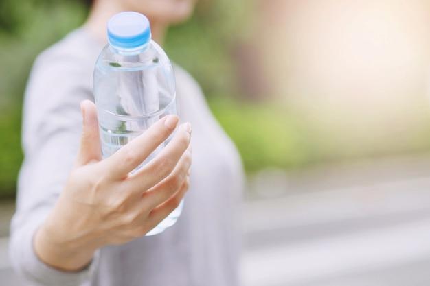 公園でプラスチックから新鮮な飲料水のボトルを持っている人々の若い手。