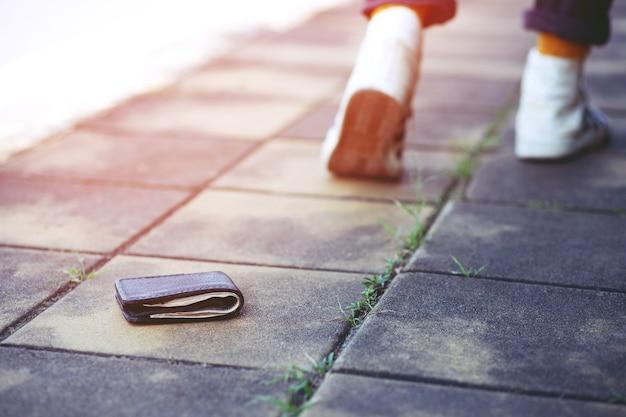 若い流行に敏感な人々は通りでお金で革の財布を失いました。旅行中の道路のコンクリートの歩道に横たわっている財布のクローズアップ。