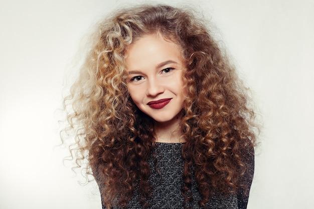 人々、若さと美しさの概念-巻き毛の大きくて長い髪の美しさの若い女性。パーマヘア。グラマーレディ、灰色の背景に美容少女。美しい女性の肖像画。ブロンドのウェーブのかかった髪