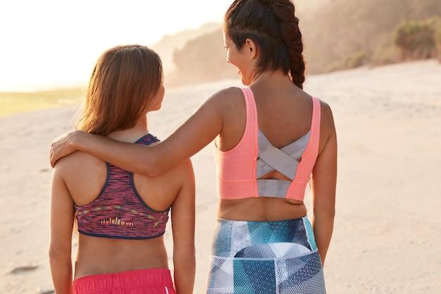 Persone, giovani, concetto di relazioni omosessuali. vista posteriore delle donne lesbiche si abbracciano mentre passeggiano in riva al mare