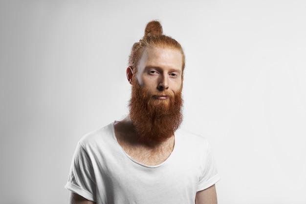 人、若者、スタイル、ファッションのコンセプト。カジュアルな白いtシャツを着て、スタジオでポーズをとっているファジーなひげと髪の結び目を持つハンサムなポジティブなトレンディな若い赤毛のヒップスターの男の写真