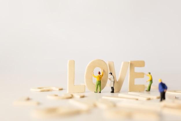 「愛」のテキスト、セレクティブフォーカス、柔らかいパステルカラートーンでバレンタインの日を準備するpeopleminiature。バレンタインの日。