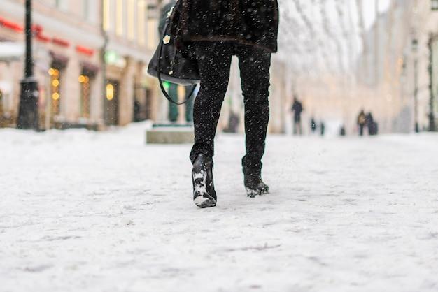 눈 덮인 날에는 부츠를 신은 사람들의 다리가 걷습니다. 도시 거리 f의 패션 컨셉