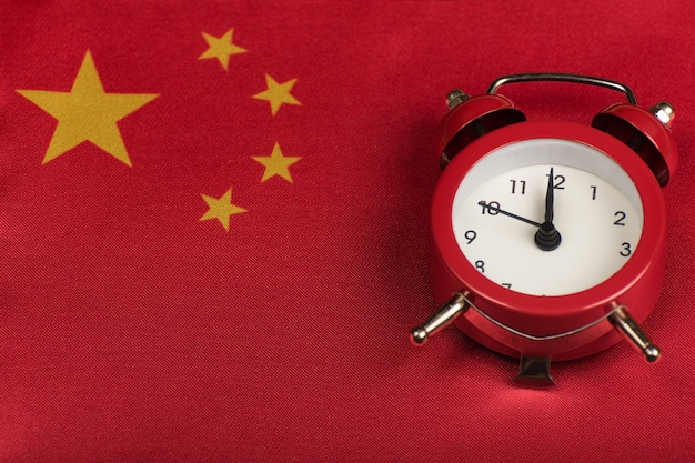 Peoples republic of china flag and vintage alarm clock close up.