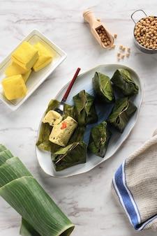 ペペスタフは、バナナの葉で包んだインドネシアのスパイス豆腐で、蒸したもので、通常は西ジャワ(スンダ)のインドネシア料理です。アジアのバジル、白い背景の蒸し豆腐