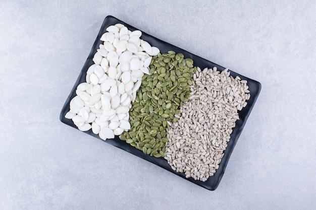 Pepitas, semi di girasole e semi di zucca bianchi su un piatto nero su superficie di marmo