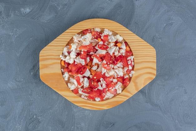 大理石のテーブルの上の小さな木製の大皿にピーマンとカリフラワーのサラダ。