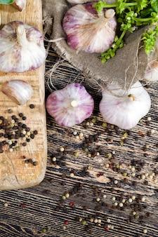 Перец и горох чеснока во время приготовления, кухонный стол во время приготовления еды, крупным планом
