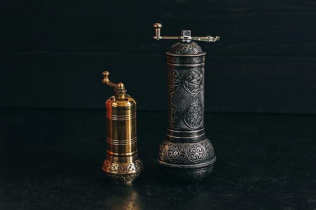 Pepper or coffee vintage metal grinder on a dark black background.