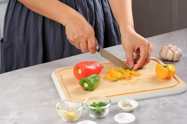コショウカッティングハンドナイフと赤緑黄ピーマン木製まな板
