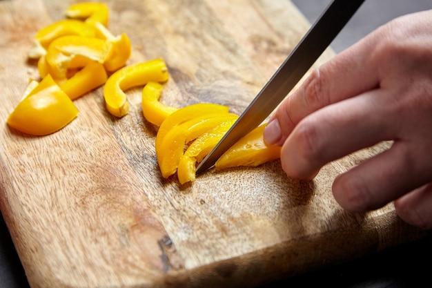 Нарезка перца. руки, нож и желтый болгарский перец, деревянная разделочная доска. кусочки сладкого перца