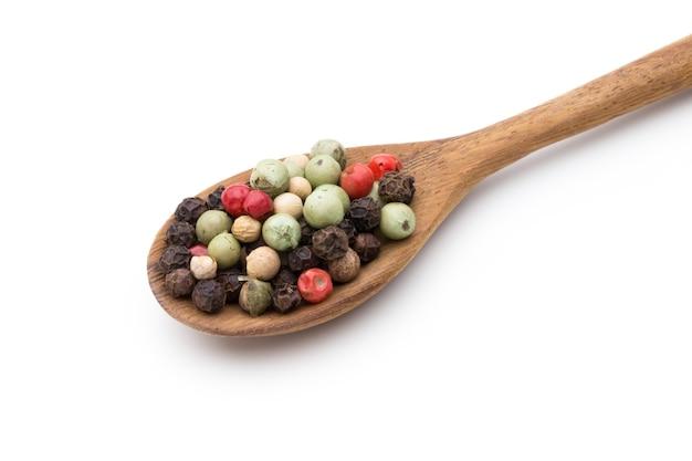 Семя смеси перца на ложке на белой предпосылке.