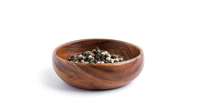 Смесь перца в деревянной миске изолированной на белой предпосылке. фото высокого качества