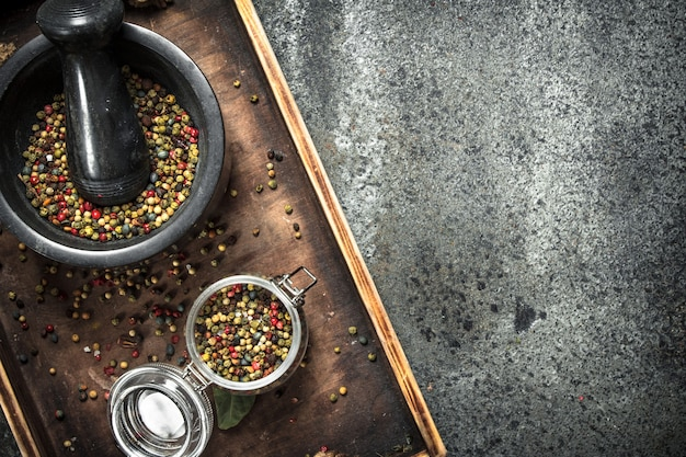 Pepper in a mortar on wooden tray on rustic table.