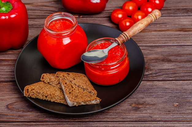 Pepper mousse from paprika and tomatoes in glass jars in a black plate on a rustic wooden table
