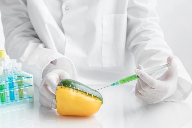 化学物質で満たされた注射器で机の上に唐辛子