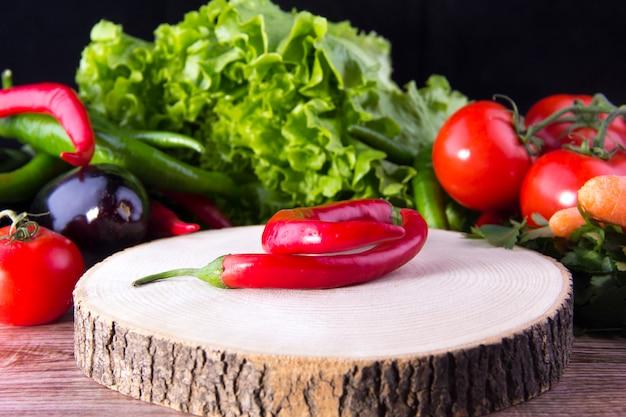 レタス、ナス、トマトの前で木の板に唐辛子
