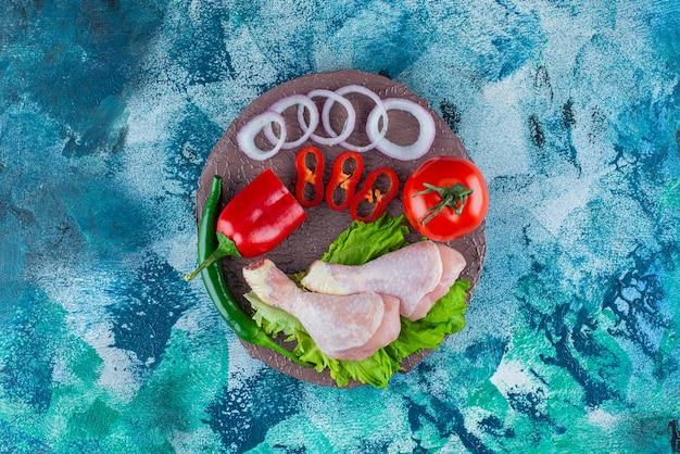青の背景に、ボード上のコショウ、オニオンリング、トマト、レタス、チキンのドラムスティック。
