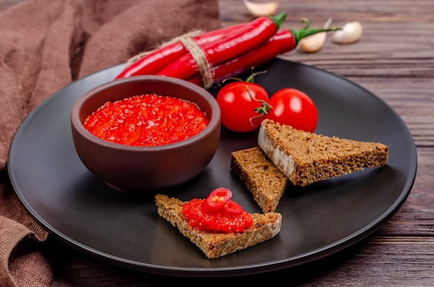 Pepper paprika and tomato mousse in a clay bowl in a black plate on a rustic wooden table
