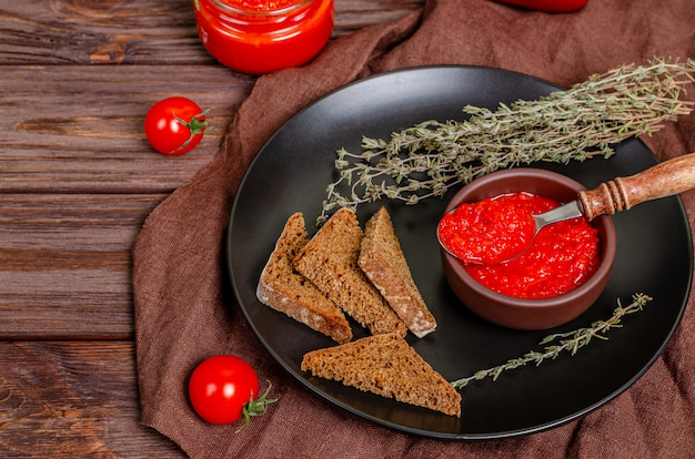 Pepper paprika and tomato mousse in a clay bowl in a black plate on a rustic wooden table.