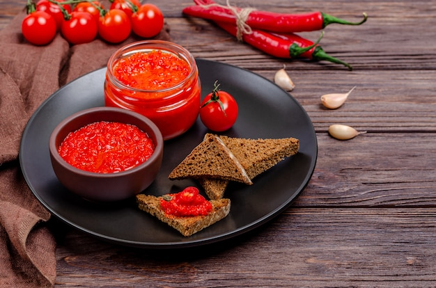 Pepper paprika and tomato mousse in a clay bowl and glass jar in a black plate on a rustic wooden table