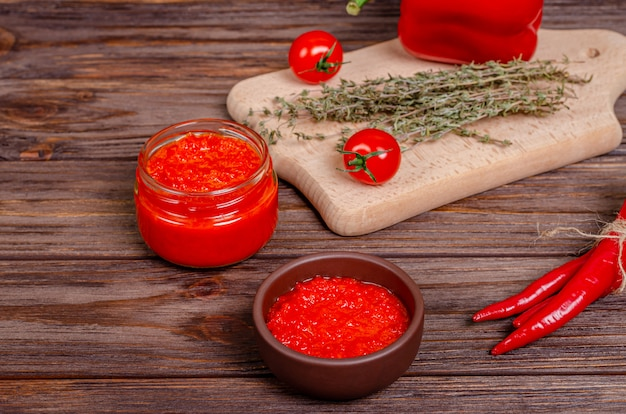 Pepper paprika and tomato mousse in a clay bowl and in a glass jar on a rustic wooden table