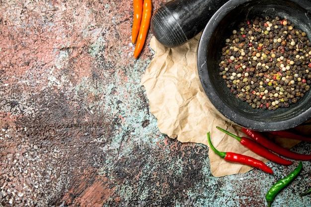 乳鉢のコショウ豆と素朴なテーブルの乳棒