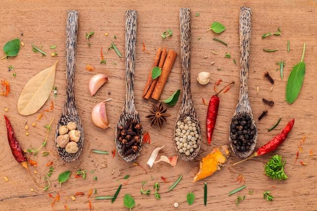 木のスプーンで黒胡pepper、白胡pepper、黒マスタード、黄色マスタード、フェヌグリーク、クミン、カレーパウダー、パプリカ、フェンネルシードのスパイスの盛り合わせ