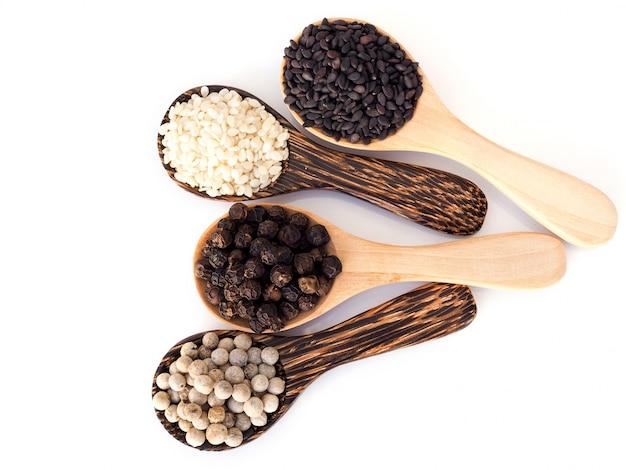 白胡pepper、黒胡pepper、黒胡麻、白胡麻の白い表面に分離された木のスプーンで穀物ハーブの平面図です。