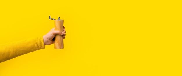 黄色の背景に手でコショウ入れ
