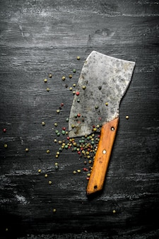 Pepper , spices and an old hatchet. on the black rustic background.