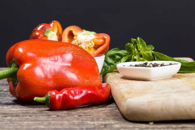 台所のテーブルの上の唐辛子のスパイス、自然で新鮮な野菜からの料理とサラダ、野菜はすべて洗浄されて汚れからきれいにされているわけではありません、食べ物のための甘いピーマンのクローズアップ