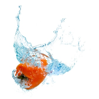 Pepper in spray of water. juicy peach with splash on white