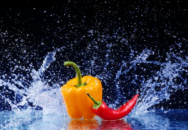 Pepper in spray of water. juicy pepper with splash on black background