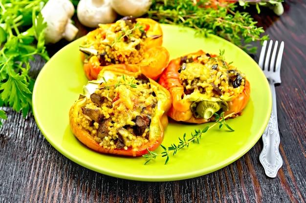 きのこ、トマト、クスクス、チーズをタオル、フォーク、木の板を背景にした緑のプレートに詰めたピーマンの甘いもの